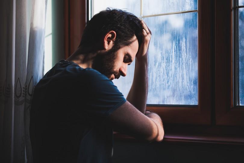 Άνδρας κοιτάζει στεναχωρημένος προς το παράθυρο